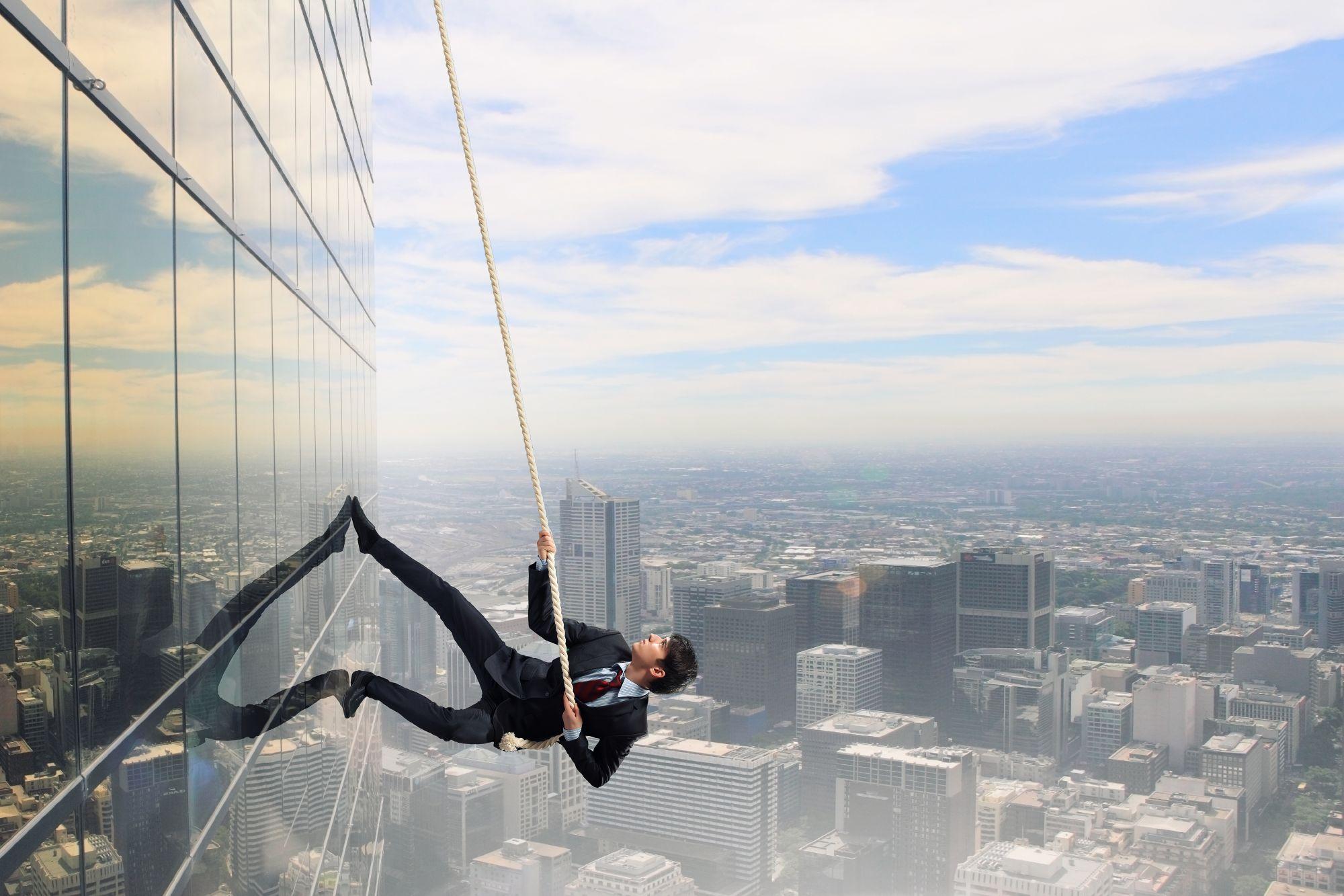 איש עסקים מטפס על קיר, אילוסטרציה למסע אל העמוד הראשון בגוגל